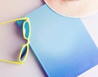 Summer set, flat lay. Book, sunglasses and straw hat, summer set Stock Image