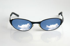 Summer shades. Sunglasses with cloud reflection royalty free stock photo