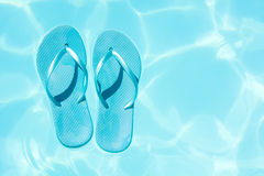 Summer shoes afloat in the swimming pool Stock Image
