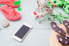 Summer shopping concept, mobile phone, woman`s accessories on sh. Opping cart on vintage wooden background royalty free stock photo