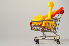 Summer shopping: Plastic sand toys in the cart Royalty Free Stock Photos