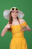 Summer shopping sale concept. Bright woman in yellow sundress and white hat showing small empty shopping cart stock images