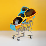 Summer shopping - Two pairs of sunglasses. Summer shopping - Blue and yellow sunglasses on the Shopping cart Stock Images