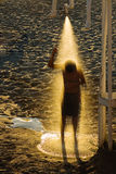 Summer shower. A boy showering on the beach before sunset with golden sunrays Royalty Free Stock Photos