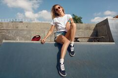 Free Summer. Skater Girl Sitting On Concrete Skate Ramp At Skatepark. Female Teenager In Casual Outfit With Skateboard. Royalty Free Stock Photography - 195691057