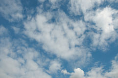 Summer skies and clouds in the UK. A few cumulus clouds, blue skies and warm weather royalty free stock image