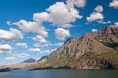Summer Skies in the Mountains. Red Eagle Mountain with summer clouds in Glacier National Park stock photos