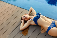 Summer skin care. Woman relaxing by the pool. Stock Photo