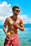 Summer Skincare. Man Applying Sunscreen Protection Body Lotion. Man Skin Care In Summer. Handsome Male With Sexy Body In Sunglasses Applying UV Protective Royalty Free Stock Photos