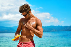 Summer Skincare. Man Applying Sunscreen Protection Body Lotion. Man Skin Care In Summer. Handsome Male With Sexy Body In Sunglasses Applying UV Protective Stock Photography
