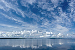 Summer Sky Reflecting in Lake. Blue summer sky with white clouds reflecting in lake stock photo
