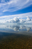 Summer Sky Reflecting in Lake. Blue summer sky with white clouds reflecting in lake stock image