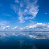 Summer sky reflecting in lake. Blue summer birght sky reflecting in lake stock image