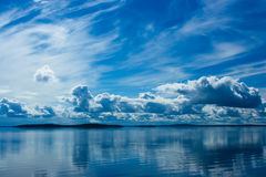 Summer Sky Reflecting in Lake. Blue bright summer sky with white clouds reflecting in lake. Srednee Kuyto Lake, Karelia, Russia stock images