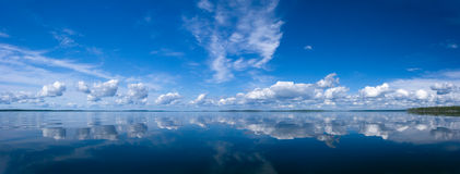 Summer Sky Reflecting in Lake. Blue bright summer sky with white clouds reflecting in lake. Srednee Kuyto Lake, Karelia, Russia stock photo