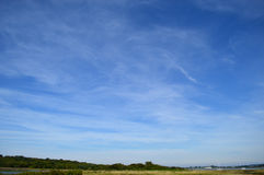 Summer sky view over marshlands at Mudeford, Dorset, United Kingdom. Whispy clouds in large blue summer sky over marshlands at Mudeford, Dorset, United Kingdom stock photo