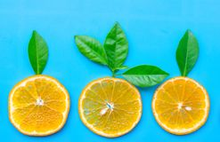 Summer of slice orange fruit with green Leaves on blue background royalty free stock photography
