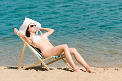 Summer slim woman sunbathing in bikini deckchair. Summer young woman sunbathing in bikini on beach Royalty Free Stock Image