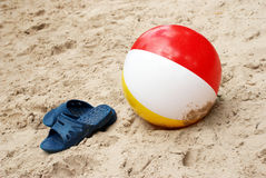 Summer slippers and Beach ball in sand Royalty Free Stock Images