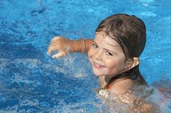 Summer smile. A cute little girl in pool water during the summer royalty free stock image