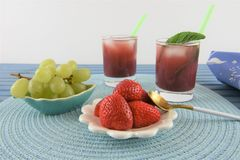 Summer smoothie cold drink in red berry and grape flavor. Glass of red fruit smoothie drink with ice and fresh mint leaf. Made with strawberry red and green royalty free stock photo