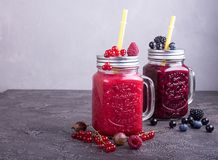 Summer smoothies of raspberries, red and black currant, goosberries, blueberries, blackberries in glasses on grey concrete royalty free stock photos