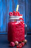 Summer smoothies of raspberries, red currant, goosberries in glasse on blue background. royalty free stock photo