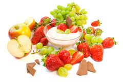 Summer snack. A bowl of yogurt with strawberries, grapes, apples and chocolate royalty free stock images