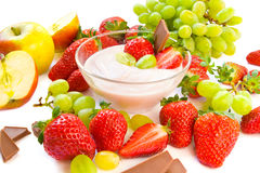 Summer snack. A bowl of yogurt with strawberries, grapes, apples and chocolate stock photo