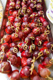 Summer snack of grapes and strawberries on skewers. A tray with fruit snacks from pieces of grapes and strawberries on bamboo skewers stock images