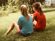 Summer snapshot 1970s style. Straight out of the old scrapbook: two ponytailed girls sit on green grass on a lazy summer day (deliberate effect of faded color Stock Images