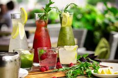 Summer soft drinks, a set of lemonades. Lemonades in jugs on the table, the ingredients of which they are made are. Arranged around royalty free stock images