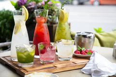 Summer soft drinks, a set of lemonades. Lemonades in jugs on the table, the ingredients of which they are made are. Arranged around royalty free stock photo