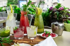 Summer soft drinks, a set of lemonades. Lemonades in jugs on the table, the ingredients of which they are made are. Arranged around royalty free stock photography