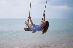 Summer solar portrait of fashion of a way of life of the young stylish woman,sitting on a swing on the beach,carrying lovely fashi Royalty Free Stock Image