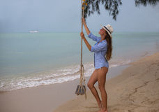 Summer solar portrait of fashion of a way of life of the young stylish woman,sitting on a swing on the beach,carrying lovely fashi Royalty Free Stock Photography