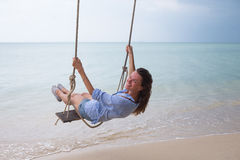 Summer solar portrait of fashion of a way of life of the young stylish woman,sitting on a swing on the beach,carrying lovely fashi Royalty Free Stock Images