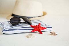 Summer, some sea stuff on white and stripped. Sunglasses, straw hat, seastar, stripped towel on white stock photography
