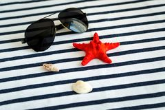 Summer, some sea stuff on white and stripped. Sunglasses, straw hat, seastar, stripped towel on white stock images