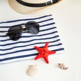 Summer, some sea stuff on white and stripped. Sunglasses, straw hat, seastar, stripped towel on white stock photos
