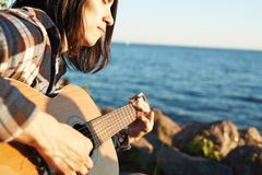 Summer song. Young man with guitar playing music by seae on summer day Stock Images