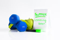 Summer soon. Dumbbell green apple and tape measure. Dumbbell green apple and soft meter. sport and training Stock Photo
