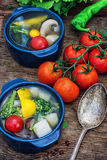 Summer soup with fresh vegetables. Traditional soup of fresh vegetables in blue pot on wooden background.Photo tinted Royalty Free Stock Photography