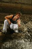 Summer splash. Slim male model in sweats goofing of on the bank of a river Stock Photo