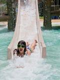 Summer splash. A teen girl having fun on a waterslide on a hot summer day Stock Photography