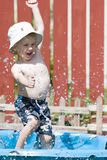 Summer splash. Boy splash through pool on hot summer day royalty free stock photos