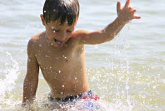Summer splashing. A little boy splashing in the water at the lake royalty free stock photo
