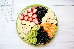 Summer sponge cake with bananas, strawberries, currants, tangerines, bilberries and kiwi.. Top view horizontal Royalty Free Stock Photo