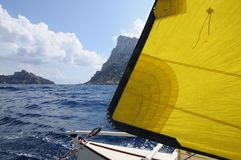 Sailing Catamaran with yellow sails in Ibiza Spain. Summer sport activity going sailing on a catamaran in Cala d'Hort, Ibiza Spain Stock Photo