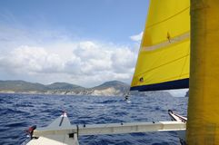 Sailing Catamaran with yellow sails in Ibiza Spain. Summer sport activity going sailing on a catamaran in Cala d'Hort, Ibiza Spain Royalty Free Stock Images